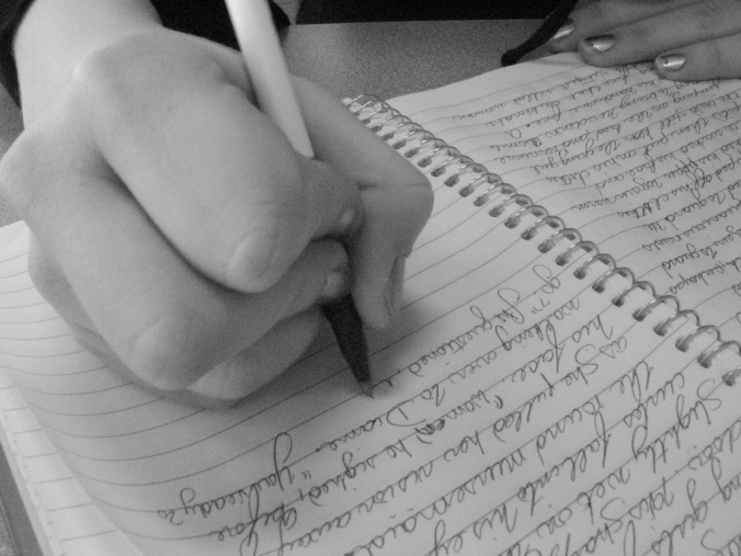 Journal being written in by a hand holding a pen