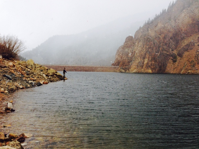 Shore of mountain reservoir with fog rolling in as fisherman waits for catch